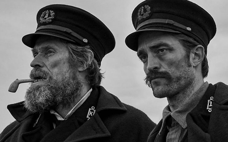 Thomas Wake (Willem Dafoe) and Ephraim Winslow (Robert Pattinson) descend into a web of power plays and madness in Robert Eggers' The Lighthouse.
